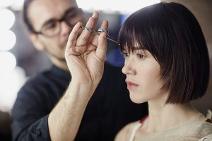 male stylist cutting woman's bangs