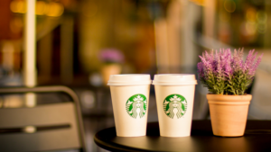 starbucks cups next to a plant