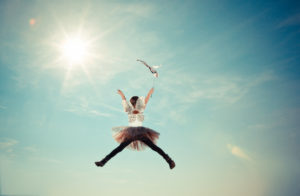 child dressed as a fairy jumping