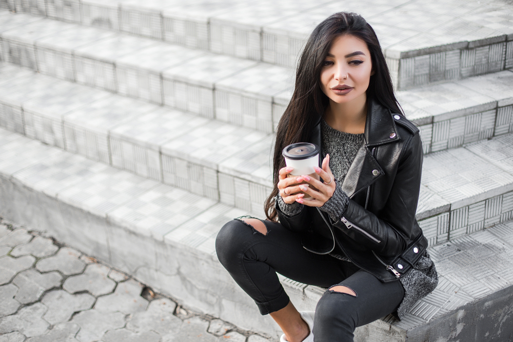 girl sitting on steps holding a coffee