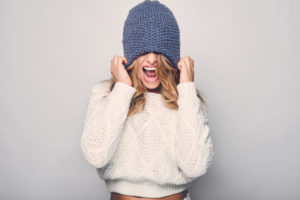 woman in knit cap pulling it over her hair