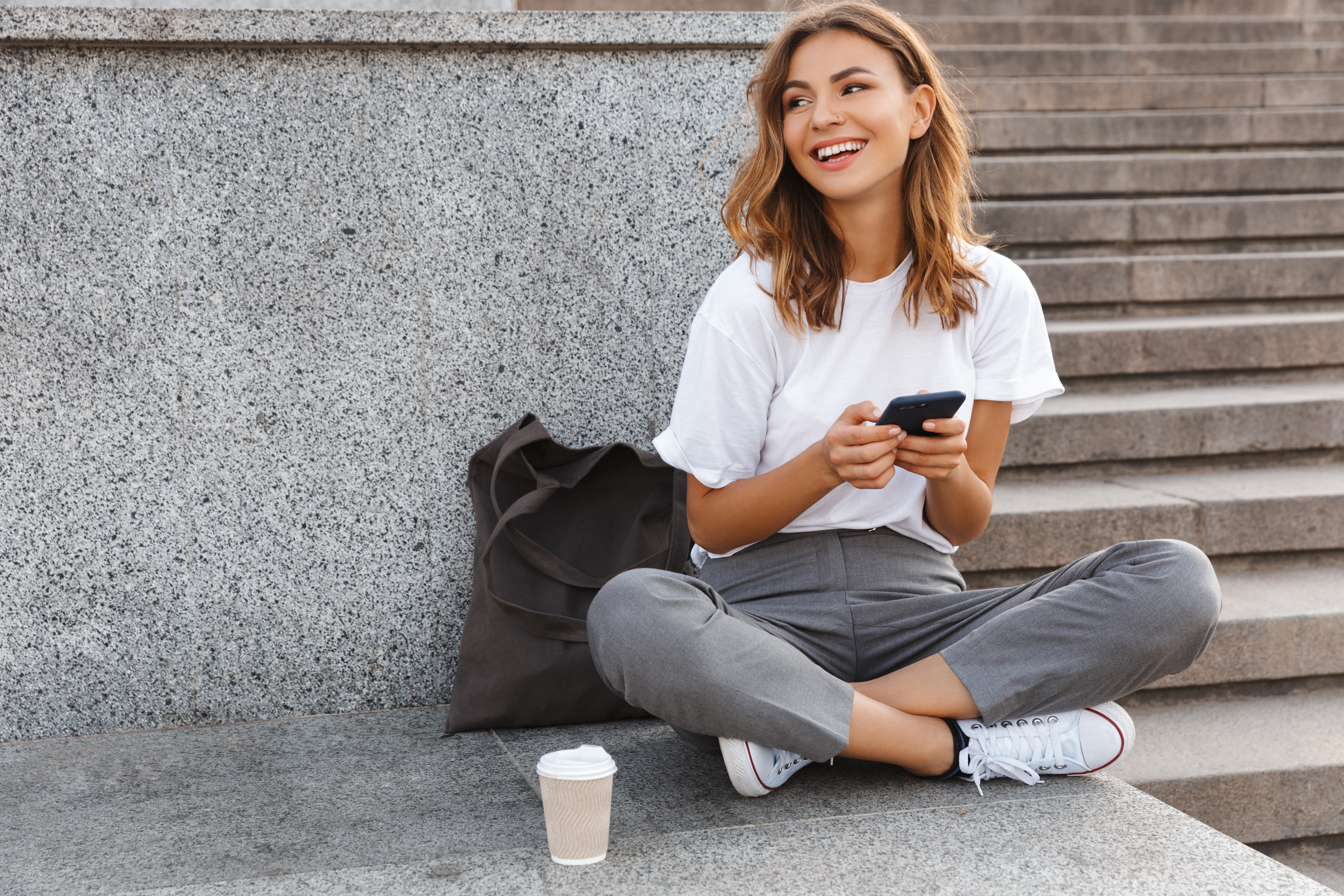 Girl sitting cross-legged outdoors holding a phone