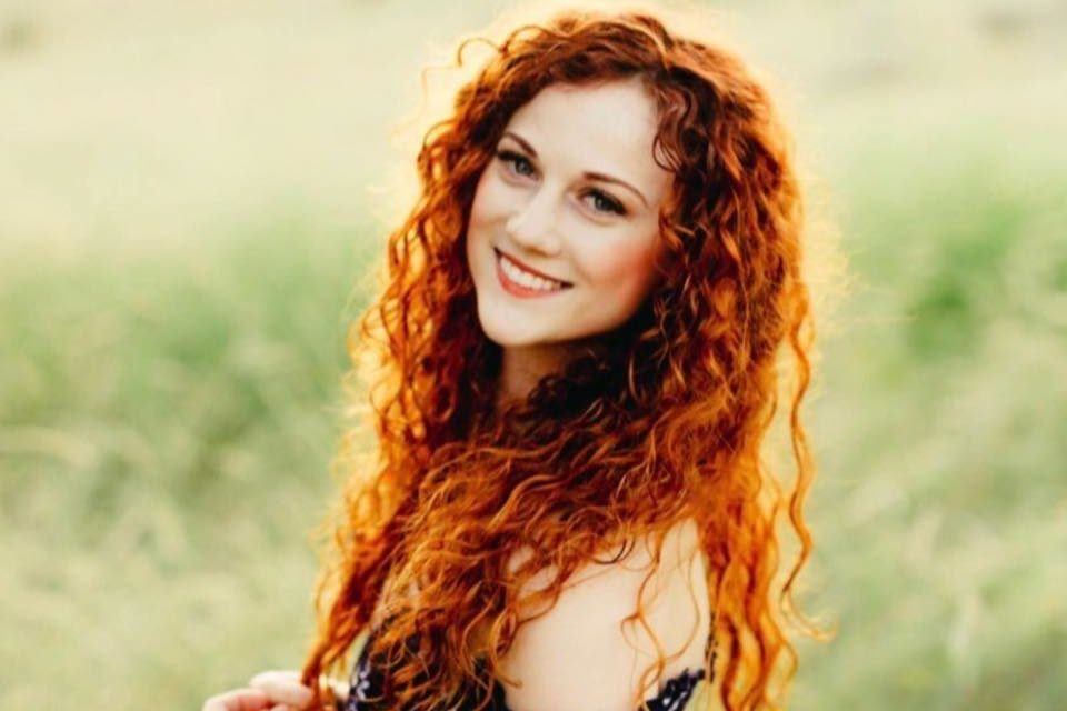 Collete Hood - An Aveda Alumni portriat of her in a green grass field wearing a dress and red long curly hair
