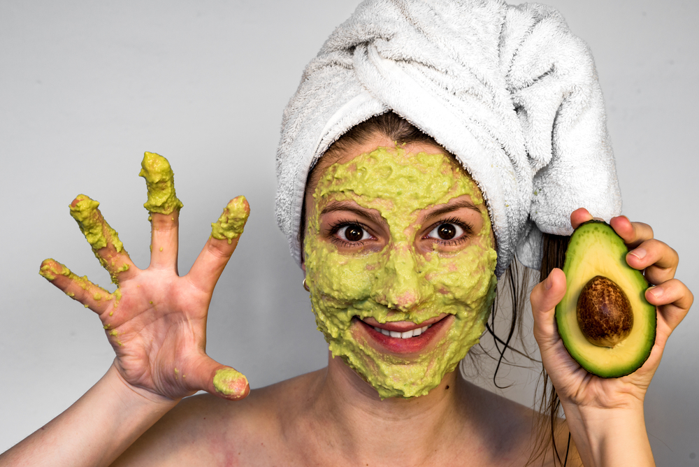 woman holding avacado with green face mask