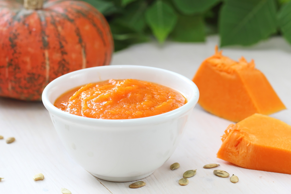 pumpkin puree in white bowl surrounded by pieces of pumpkin