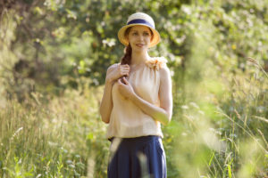 woman wearing vintage clothing and hat walking in a meadow