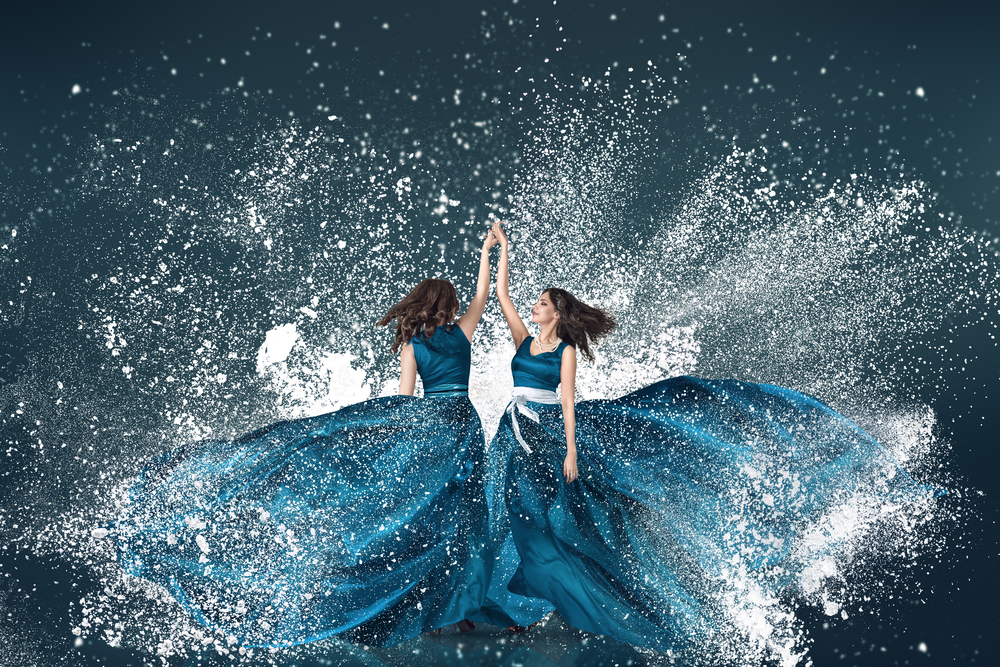 two women dancing in gowns look like waves