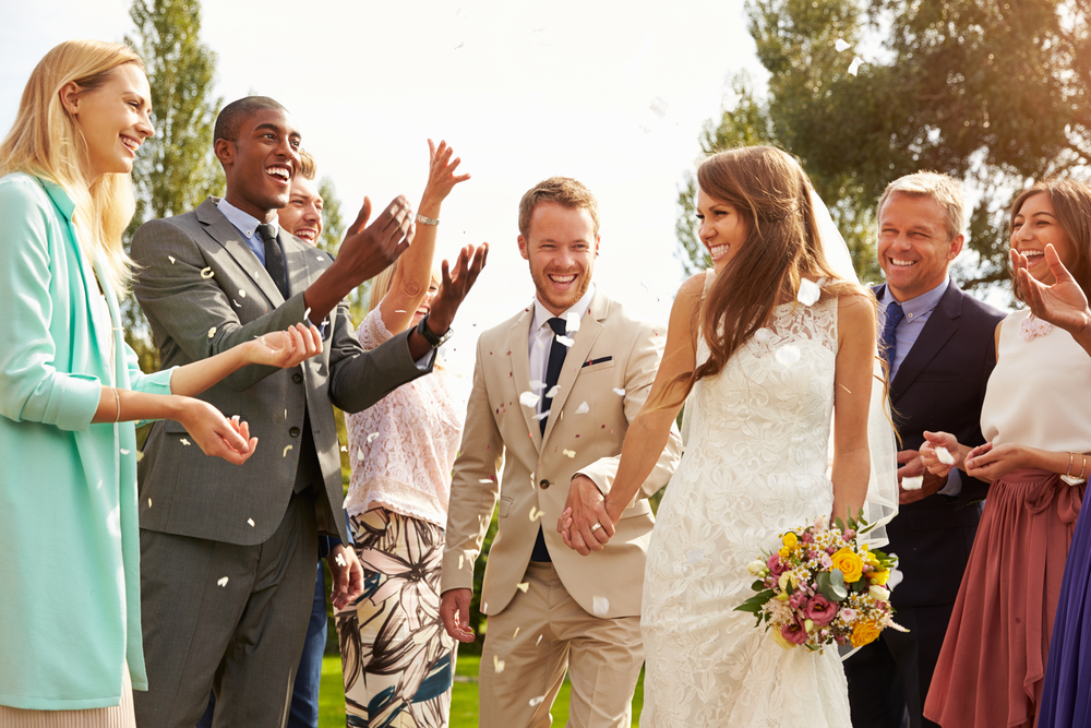 wedding party bride and groom holding hands surrounded by guests