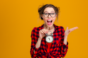 A confused woman holding a clock, because clocks have hours, and hours are cool- but also very confusing.