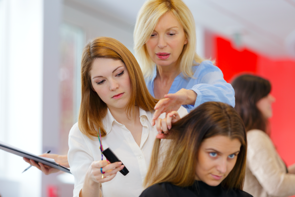 A cosmetology instructor helping a student to master a skill