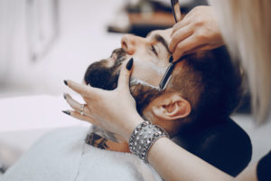 Female barber shaving male client's beard with straight razor