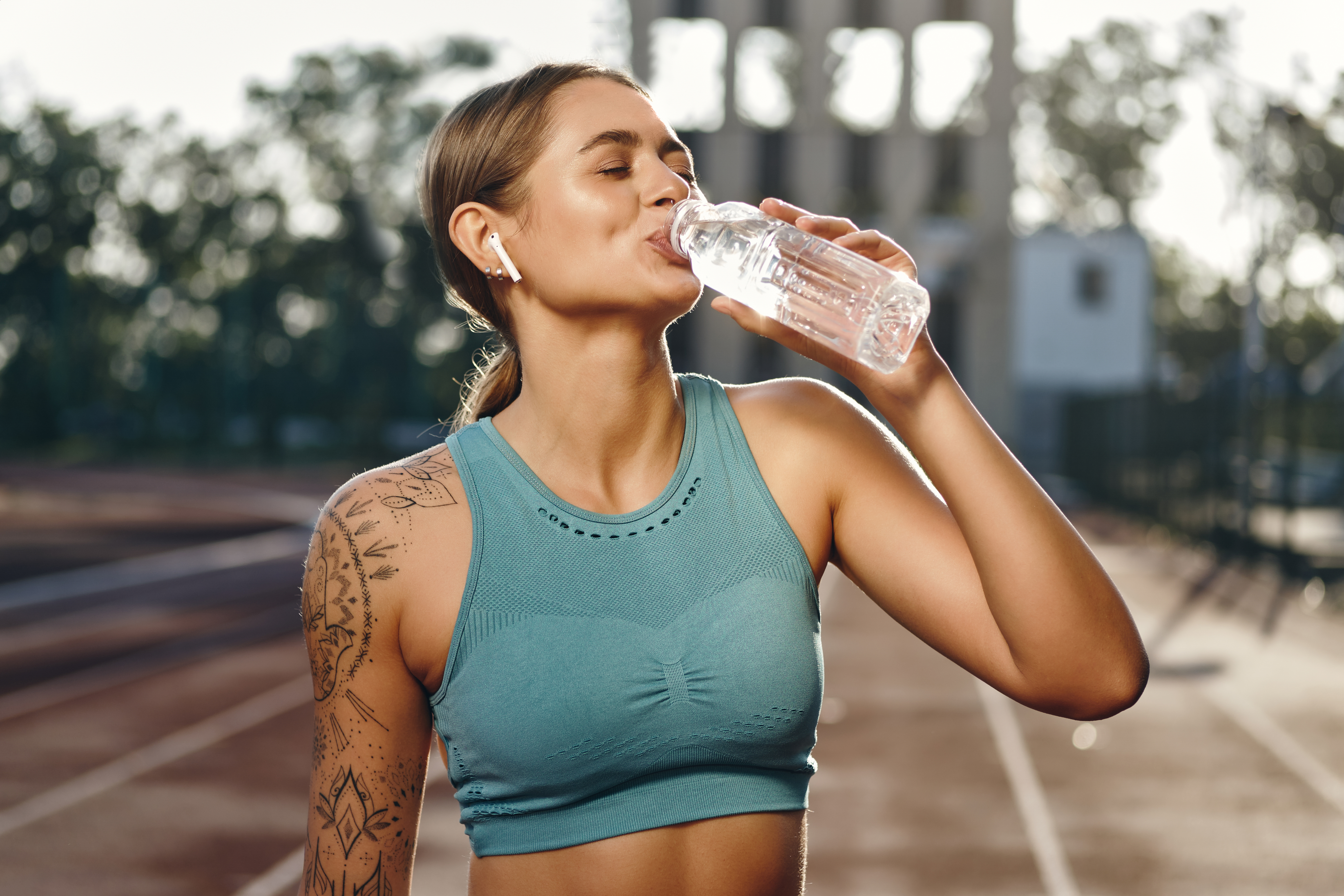 tatooed woman on racetrack takes a drink of water