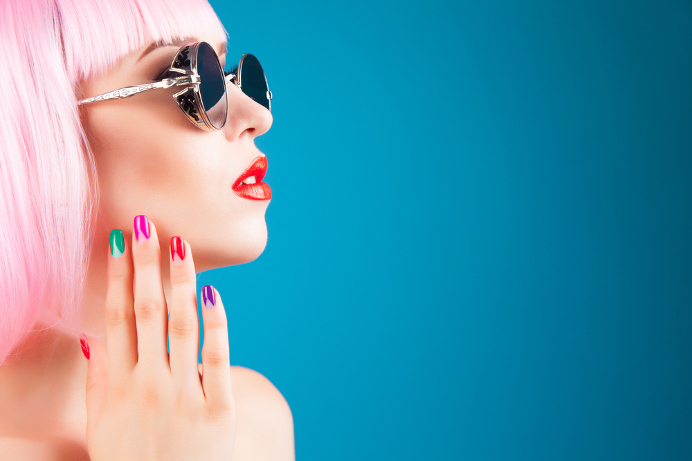model with pink hair and glasses modeling a side profile with her fingers touching her chin
