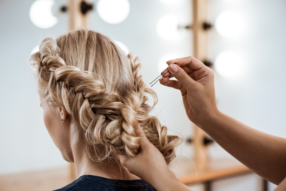 cosmetologist pinning woman's hair up