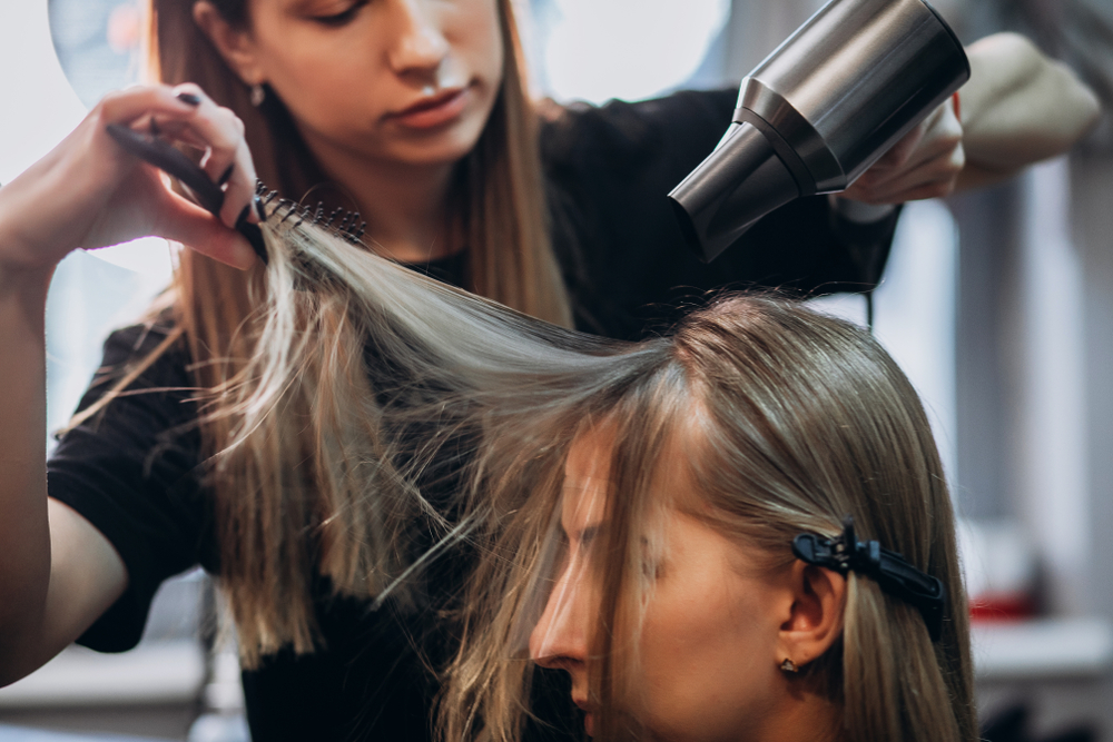 cosmetologist helping client with hair